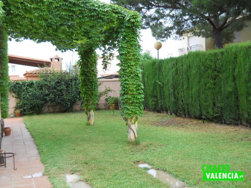 Jardín con césped, cipreses y enredadera fachada chalet