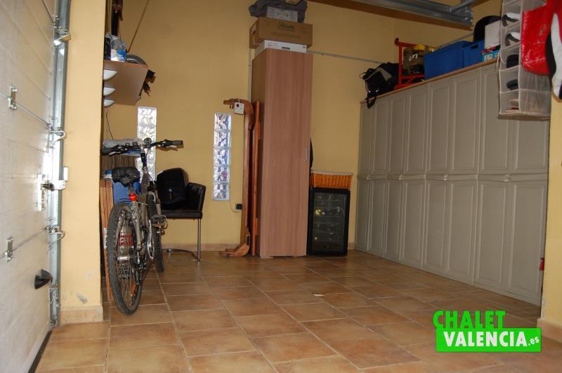 Garaje con puerta automática y espacio para coche y almacén